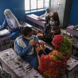 Un trabajador sanitario inocula a un estudiante con una dosis de la vacuna de Pfizer contra el coronavirus Covid-19 en una escuela de Lahore, después de que el gobierno iniciara una campaña de vacunación de niños a partir de 12 años.   Foto:Arif Ali / AFP