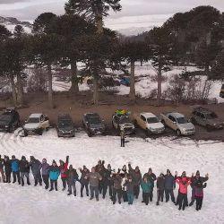 Los 35 participantes parados sobre la laguna congelada Corazón saludan al dron de @bydroneye.