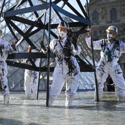 """Activistas de Greenpeace vestidos con el uniforme de los trabajadores del petróleo se sitúan junto a una """"torre de pozo de petróleo"""" humeante durante una acción frente a la pirámide del Museo del Louvre en París, mientras protestan contra la compañía energética francesa Total y la continua producción y consumo de combustibles fósiles en el mundo.   Foto:Anne-Christine Poujoulat / AFP"""