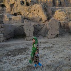 Una niña de la etnia Hazara pasa por delante de los acantilados plagados de cuevas donde la gente sigue viviendo como hace siglos en Bamiyán.   Foto:Bulent Kilic / AFP