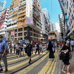 Esta foto tomada con un objetivo ojo de pez muestra a personas cruzando una calle en el distrito de Wanchai de Hong Kong.   Foto:Peter Parks / AFP