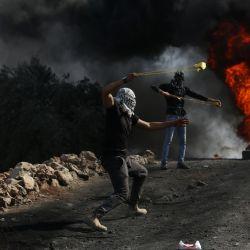 Manifestantes utilizan hondas para lanzar piedras a soldados israelíes tras una protesta en contra de la expansión de asentamientos judíos, en la aldea de Beita, en el sur de la ciudad cisjordana de Naplusa.   Foto:Xinhua/Ayman Nobani