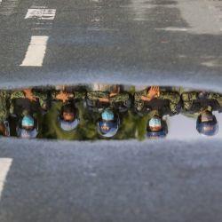 Oficiales de la Policía Nacional Filipina se reflejan en un charco de agua mientras aseguran la zona que conduce a la presentación de los certificados de candidatura para las elecciones de mayo de 2022, en la Ciudad de Pasay, Filipinas.   Foto:Xinhua/Rouelle Umali