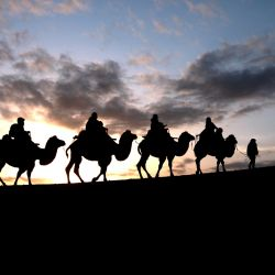 Turistas montan camellos en el área escénica del Manantial Luna Creciente en la Montaña Mingsha, en la provincia de Gansu, en el noroeste de China.   Foto:Xinhua/Zhang Xiaoliang