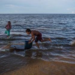 Unos niños juegan en la orilla del Lago de Maracaibo en Ologa, estado de Zulia, Venezuela. - Los habitantes de Ologa se enfrentan a un grave problema por la falta de educación, aunque está lejos de ser su principal problema ya que, desde hace tiempo, también sufren la falta de electricidad, agua y gas doméstico.   Foto:Federico Parra / AFP