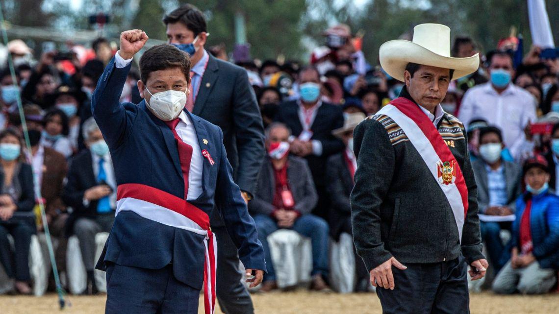 In this file photo taken on July 29, 2021, Guido Bellido (left) raises his fist next to Peru's President Pedro Castillo (right) at Pampa de la Quinua in Ayacucho, southern Peru.