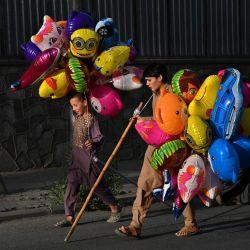 Jóvenes vendedores de globos caminan mientras buscan clientes en una calle de Kabul. | Foto:WAKIL KOHSAR / AFP