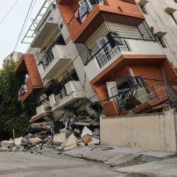 Un miembro del cuerpo de bomberos observa el derrumbe de un edificio de apartamentos de varias plantas, sin que se hayan registrado víctimas, en Bangalore. | Foto:Manjunath Kiran / AFP