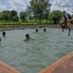 Un niño se sumerge en un tanque de agua abierta en una granja en las afueras de Bangalore. | Foto:Manjunath Kiran / AFP