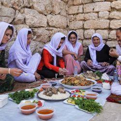 Miembros de la comunidad religiosa yazidí comparten una comida juntos mientras visitan el templo de Lalish, el más sagrado de la fe, en el valle de Lalish, cerca de la ciudad kurda iraquí de Dohuk, durante las celebraciones de la fiesta de la  | Foto:Ismael Adnan / AFP