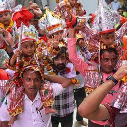 Los hombres llevan a sus hijos para honrar al dios hindú Hanuman mientras presentan sus respetos con motivo del 'Langoor Mela' en el histórico templo de Durgiana en Amritsar. | Foto:Narinder Nanu / AFP