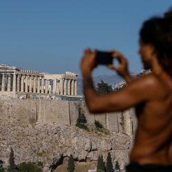 Un hombre hace una foto desde una colina con vistas al sitio arqueológico de la Antigua Acrópolis en Atenas, Grecia. | Foto:DAVID GANNON / AFP