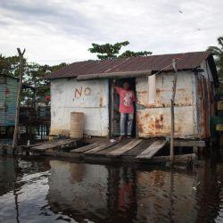 Un hombre se encuentra en la puerta de su casa en zancos sobre el lago de Maracaibo en Ologa, estado de Zulia, Venezuela. | Foto:Federico Parra / AFP