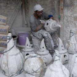 Un trabajador detalla una figura de yeso con motivos de Halloween previo a su celebración, en el taller de artesanías de la familia Galván, en la Ciudad de México, capital de México.   Foto:Xinhua/Ricardo Flores
