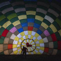 Una persona prepara un globo aerostático durante el primer Festival del Globo, en el municipio de Atlixco, en el estado de Puebla, México. | Foto:Xinhua/David de la Paz