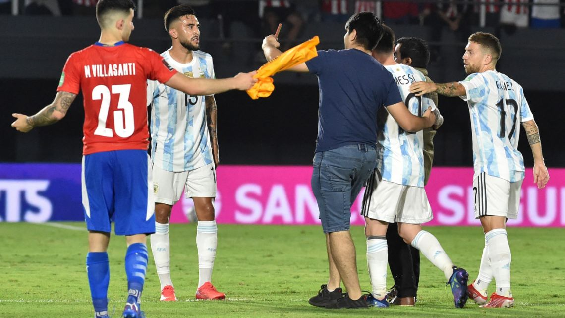 A Paraguayan fan enters to the field to take a selfie with Argentina's Lionel Messi during the South American qualification football match for the FIFA World Cup Qatar 2022 between Paraguay and Argentina at the Defensores del Chaco stadium in Asunción on October 7, 2021.