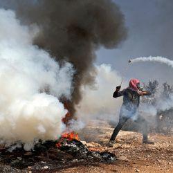 Un manifestante palestino utiliza una gomera para devolver una bomba de gas lacrimógeno hacia las fuerzas de seguridad israelíes durante los enfrentamientos que siguieron a una manifestación contra los asentamientos en el pueblo de Beita, en la Cisjordania ocupada. | Foto:Jaafar Ashtiyeh / AFP