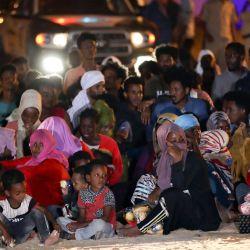 Migrantes africanos se reúnen en un refugio improvisado en el suburbio de Ain Zara. - A finales de la semana pasada, las autoridades libias asaltaron múltiples casas y refugios improvisados en un suburbio pobre de Trípoli, en lo que dijo ser una operación antidroga. Según la ONU, las redadas, dirigidas en su mayoría a inmigrantes irregulares, dejaron al menos un muerto, 15 heridos y más de 5.000 detenidos. | Foto:Mahmud TURKIA / AFP