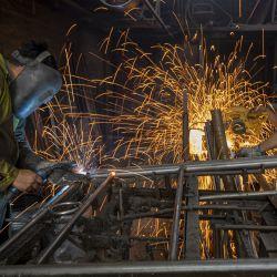 Trabajadores ensamblan tubos para la elaboración de una cama en la Fábrica Los Pepez, en Nezahualcóyotl, México. | Foto:Xinhua/Ricardo Flores