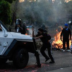 Una persona se manifiesta frente a un vehículo de la policía antimotines durante una protesta, en Santiago, capital de Chile. | Foto:Xinhua/Jorge Villegas
