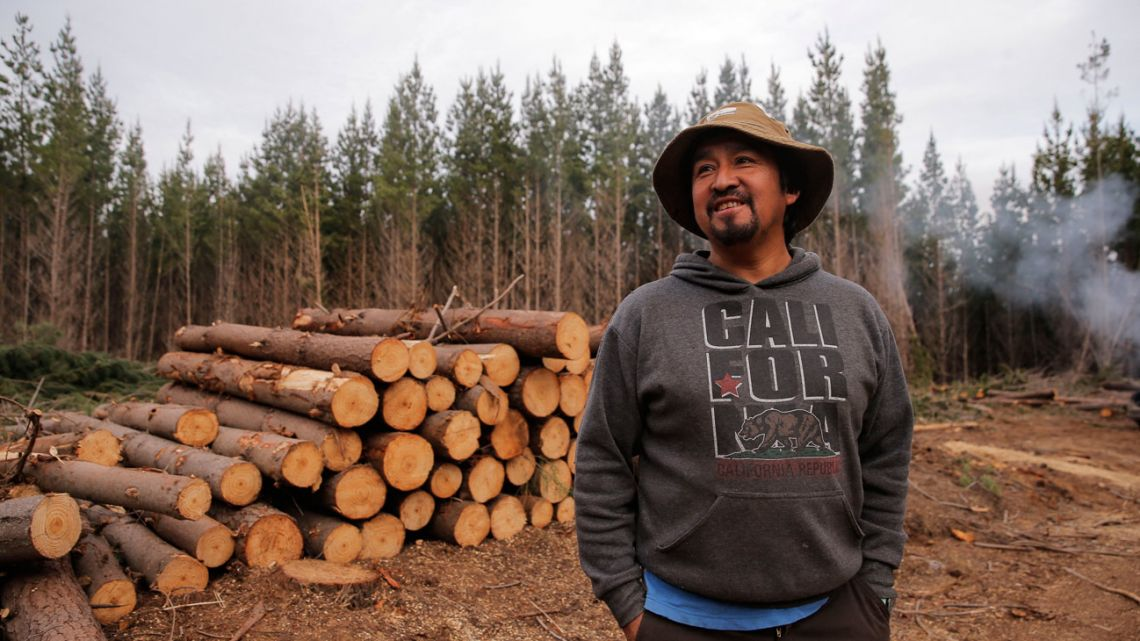 """Indigenous leader of the Mapuche radical group Coordinadora Arauco Malleco (CAM) Juan Pichùn stands next to freshly felled trees during the illegal occupation of the lands of a forestry company in Traiguen, Araucanía Region, Chile, on September 28, 2021. Pichùn, who doubts that a new constitution will resolve the Mapuche people historic demands for land and self-determination, took """"territorial control"""" of the place along with 30 members of CAM, and cut down dozens of trees that they would later sell."""