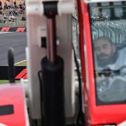 Un trabajador descansa mientras el piloto de Ferrari, Charles Leclerc, conduce durante una sesión de prácticas en el Intercity Istanbul Park en Estambul.   Foto:Andrej Isakovic / AFP