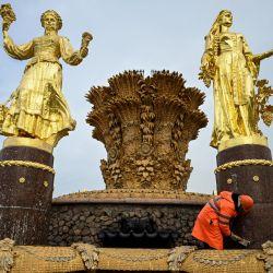 Un trabajador municipal limpia la fuente Druzhba Narodov (Amistad de las Naciones) en el Centro de Exposiciones de Rusia como parte de los preparativos de la ciudad para el invierno en Moscú.   Foto:Kirill Kudryavtsev / AFP
