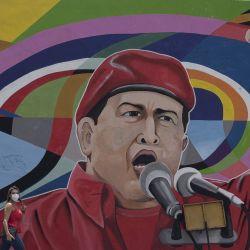 Una mujer camina frente a un mural con la imagen del expresidente venezolano, Hugo Chávez, en Caracas, Venezuela.   Foto:Xinhua/Marcos Salgado