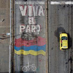 """Vista aérea de un coche y motocicletas que pasan por delante de una pintura en la que se lee """"Viva la huelga"""" en una calle de Cali, Colombia.   Foto:Luis Robayo / AFP"""