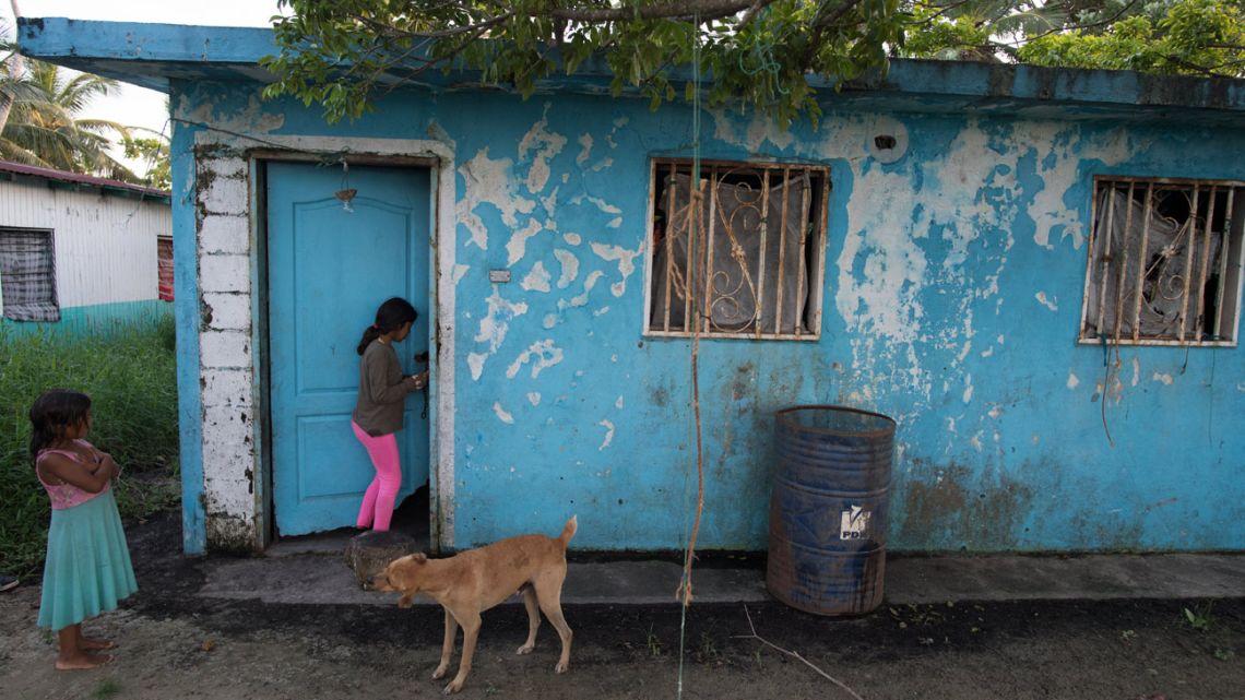 A girl opens the door of the public school of Ologá, Zulia state, Venezuela, on September 6, 2021.