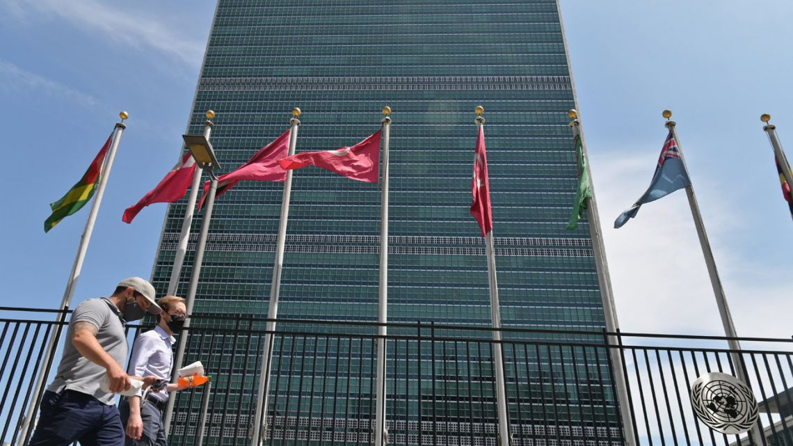 In this file photo taken on May 20, 2021, people walk past flags outside the United Nations headquarters in New York City.