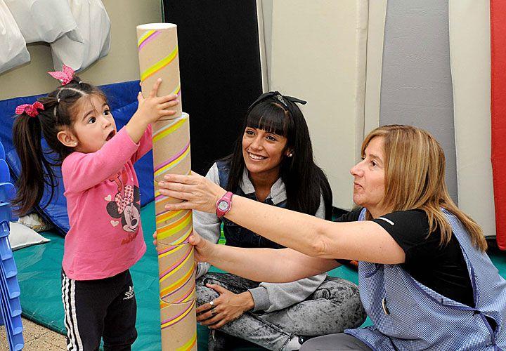 Juegos. Noelí (20), su hija y la maestra de la sala de la Escuela 2 de La Plata comparten un recreo.
