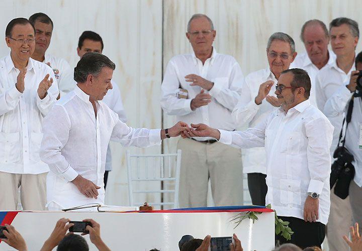 Histórico. El presidente Juan Manuel Santos y el máximo líder de las FARC sellaron con una foto el pacto del alto el fuego bilateral y definitivo en Colombia. Paz, un pedido de todos los habitantes del país, y el homenaje a quienes perdieron su vida por esta guerra.