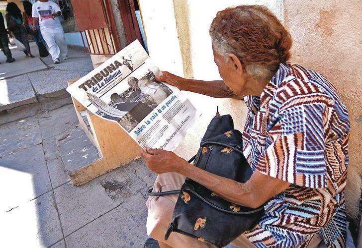Una mujer lee un periódico estatal en Centro Habana. La prensa oficial se ha envalentonado por las declaraciones de Castro en el sentido de que los medios deben ser más críticos.