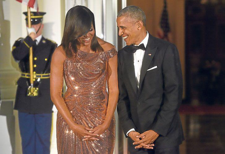 Complicidad. Obama junto a Michelle con un vestido metálico de Versace que hará historia.