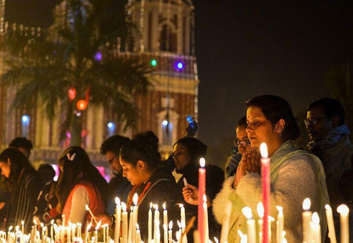 La gente de la India encender velas durante un servicio de Nochebuena en la Catedral del Sagrado Corazón en Nueva Delhi el 24 de diciembre de 2016. Aunque los cristianos indios representan sólo un dos por ciento de la población del país más de mil millones, la Navidad se ha convertido en un festival popular en el calendario indio.