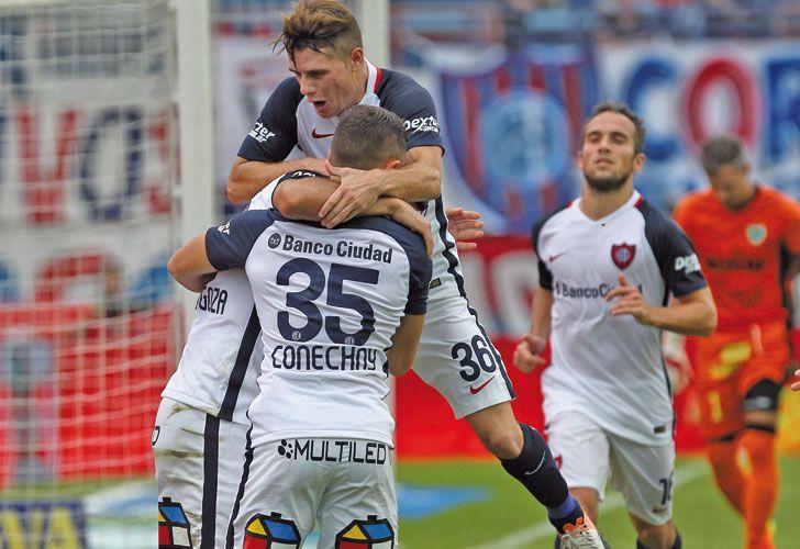 Todos con Ortigoza. El autor del gol recibe los abrazos sus compañeros. El Ciclón sigue en carrera.