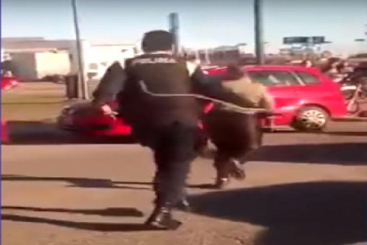 El policía corre a la mujer a latigazos.