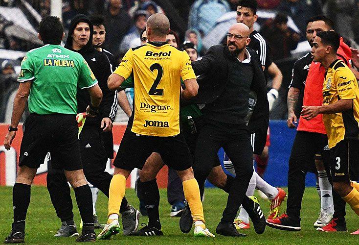 Manual de tramposos. Jugadores y técnicos de Comunicaciones y Riestra en plena batalla; el local invadió la cancha con el objetivo de terminar el partido.