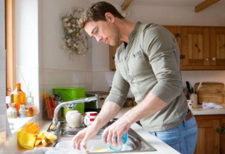 A lavar los platos. Promueven el reparto de las tareas del hogar.