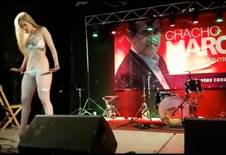 Show de strippers delante de los carteles de campaña del candidato.