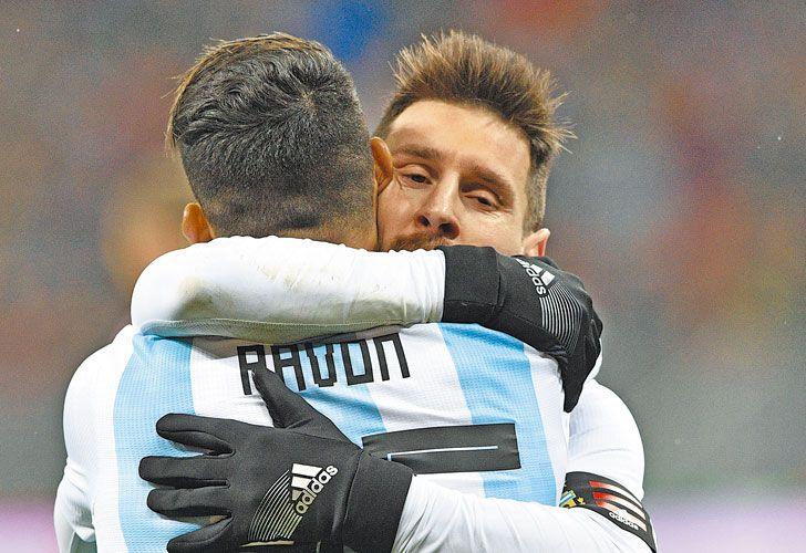 Abrazo de socios. Messi abraza y festeja junto a Pavón, que le sirvió el gol a Agüero en el final del partido contra los rusos.