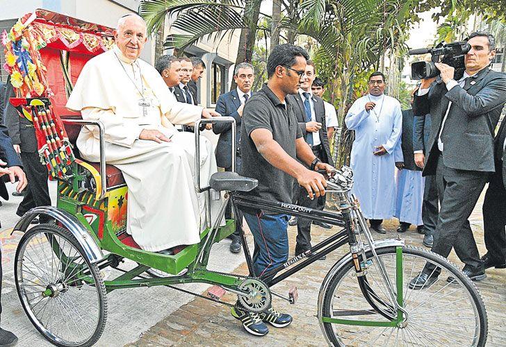 """en ciclotaxi. Bergoglio paseó ayer en """"rickshaw"""", el tradicional medio de transporte utilizado en Bangladesh. Minutos después, expresó su apoyo a los refugiados."""