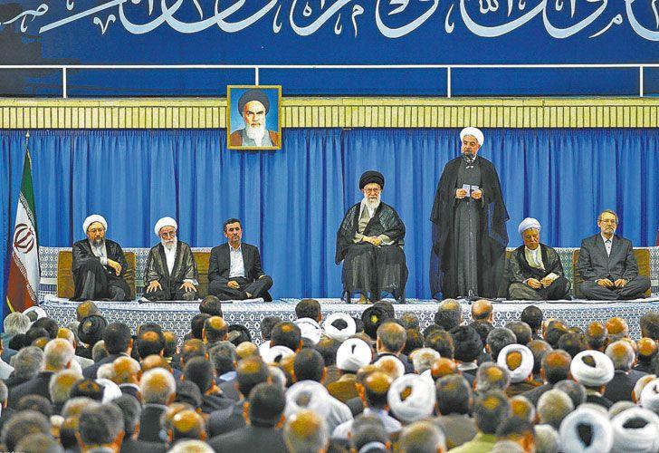 Dos hombres en pugna. Alí Jamenei (sentado al centro) y Hasan Rohani (de pie) evidenciaron su discrepancia sobre las manifestaciones. Estilos contrapuestos.