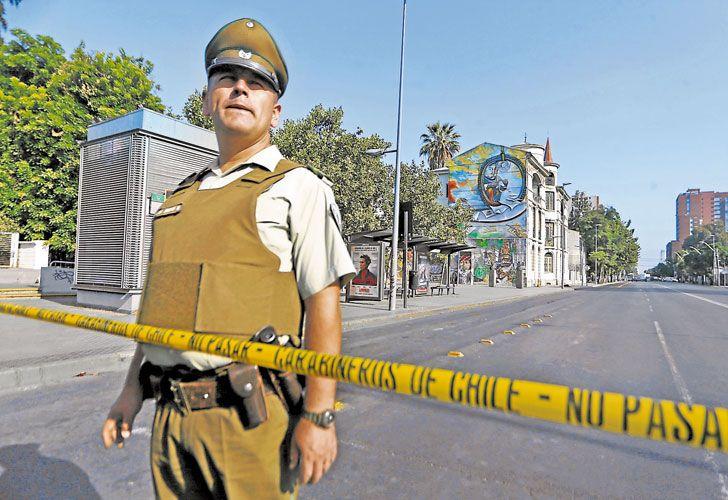Custodia. Un carabinero hace guardia en una de las iglesias que sufrieron atentados en Santiago.