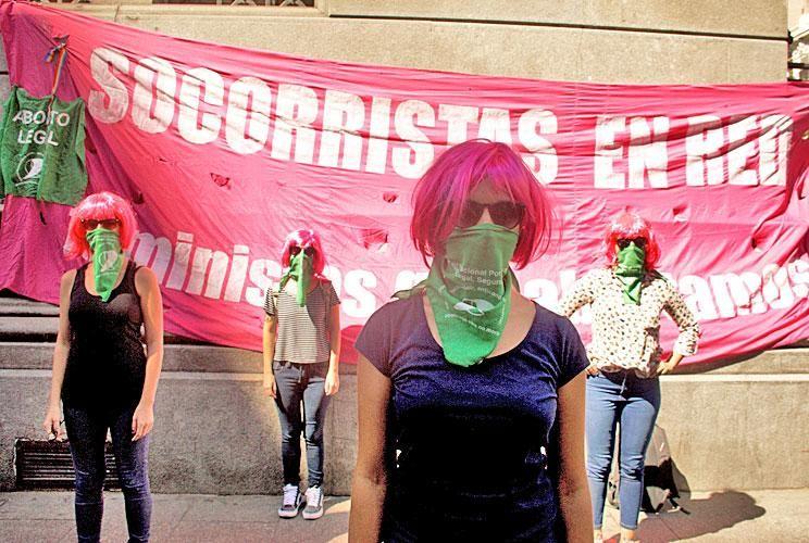 Pelucas rosadas. Es el distintivo que las identifica. En la foto, socorristas platenses que cuentan sus experiencias cubren sus caras con los pañuelos verdes por el aborto legal.