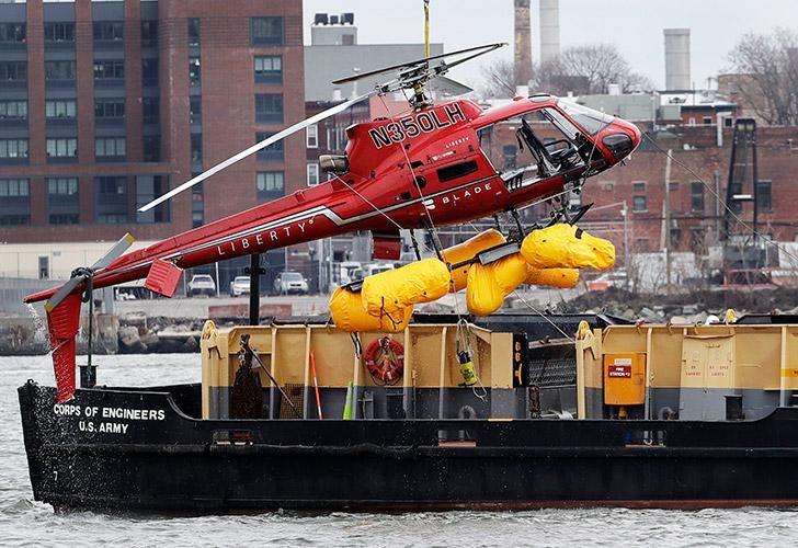 Un helicóptero es levantado por una grúa desde el East River hacia una barcaza.