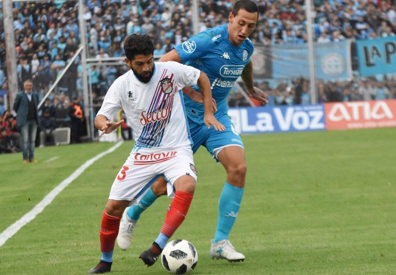 Defensor y goleador. Cristian Lema persigue a Lucas Wilchez. En el área rival, el zaguero de Belgrano fue determinante.
