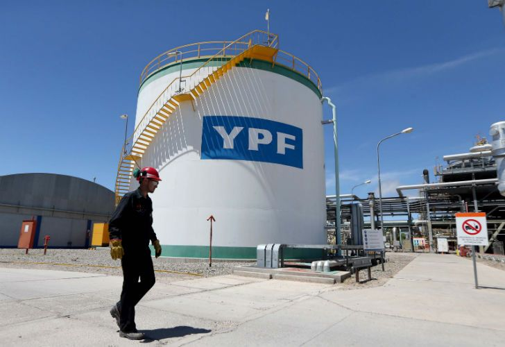A worker walks past a YPF oil tank in Neuquén