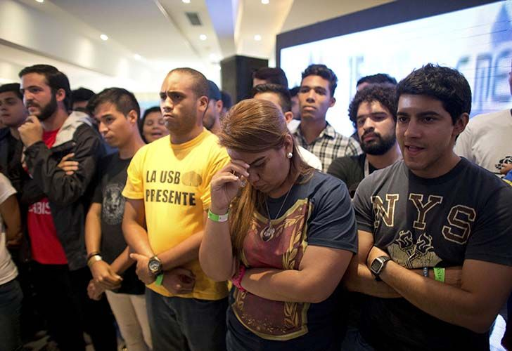 Opposition members react as the President of Venezuelan National Electoral Council Tibisay Lucena announces that the candidates for the ruling socialist party have won a majority of the 23 governors' offices up for grabs in regional elections at MUD headquarters in Caracas, Venezuela on Sunday.